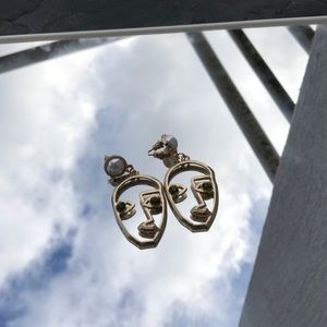 Gold face shaped earrings